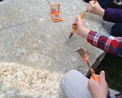 elementary students carving compass rose on granite boulder with hammer and chisel during Drystone Joe artist residency